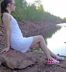 Junge Frau mit Brille und Kleid sitzt auf einem Stein